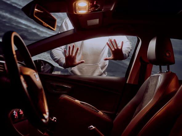 Dieb an Autoscheibe möchte in den Wagen einbrechen.