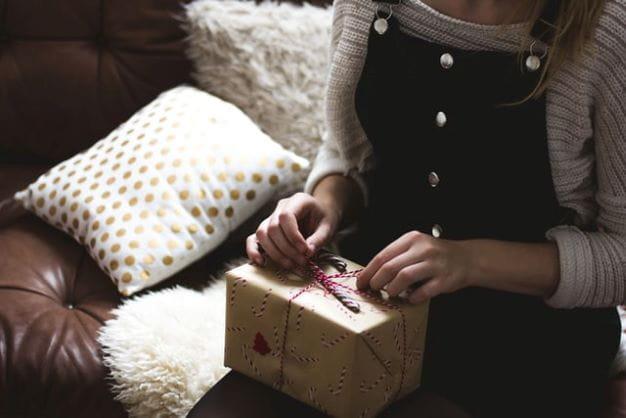 Frau öffnet Geschenk, welches symbolisch das Pack Opening im Fifa darstellt.