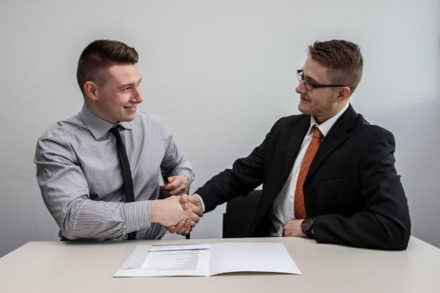 2 Menschen besiegeln eine neue Partnerschaft per Handschlag.