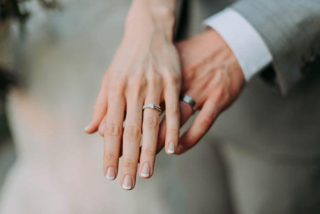 Eheringe an den Händen als Symbol für den Ehebund.