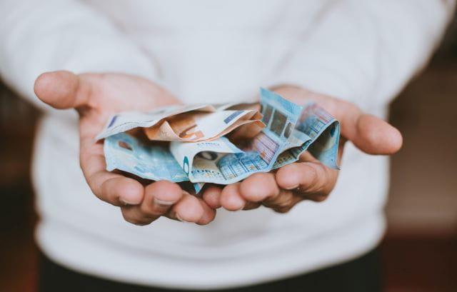 Geld auf der Hand welches Spenden-Gelder symbolisiert.